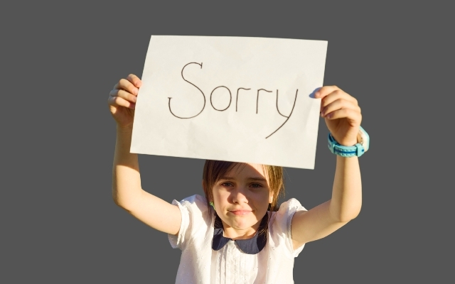 a girl holding an apology board with both of her hands