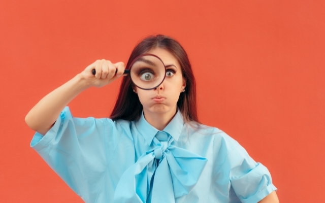 a girl looking through a magnifying glass with critical eyes