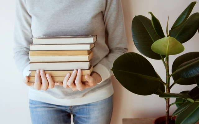 a girl standing by a wall and holding a few books with both of her hands