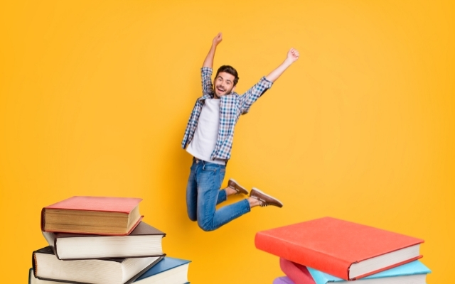 a man jumping high in the air after finishing assignment of reading books