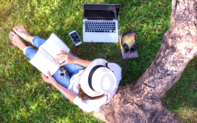 a woman sitting under a tree and reading a book