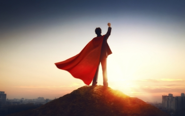 superman standing on top of a hill and raising his right hand making a fist
