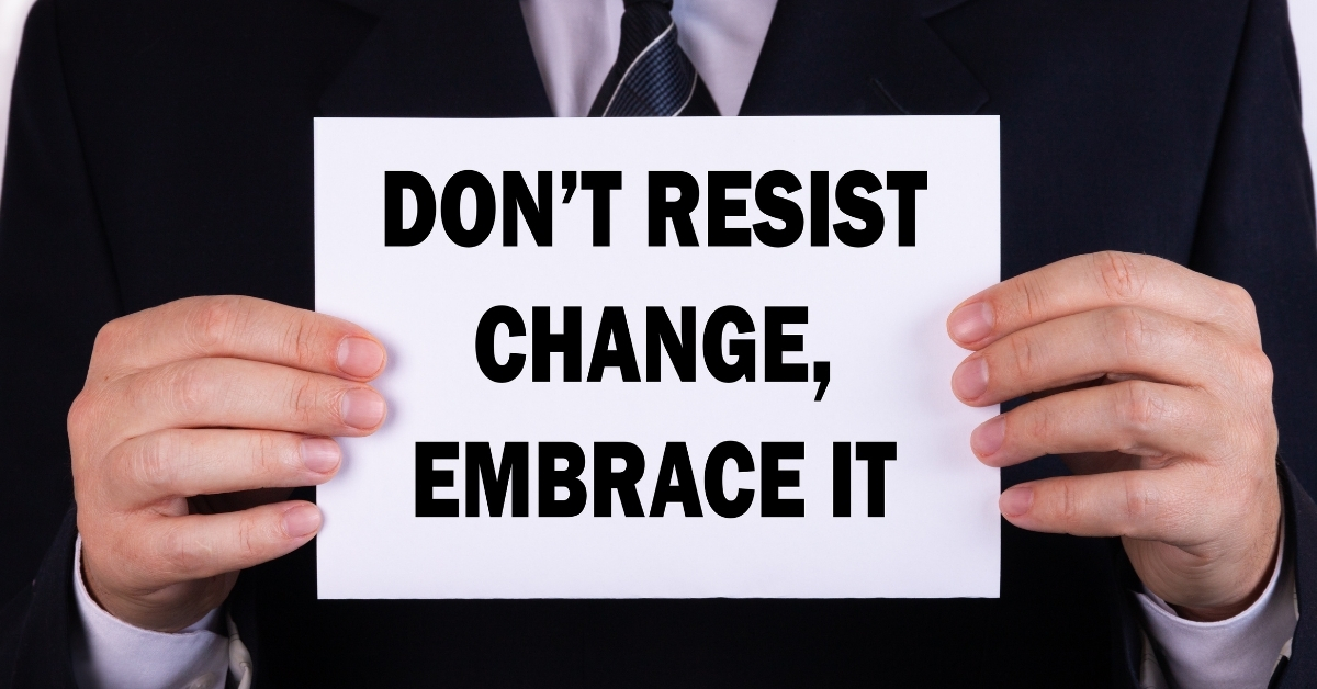 a manager holding a messge that says don't resist change embrace it