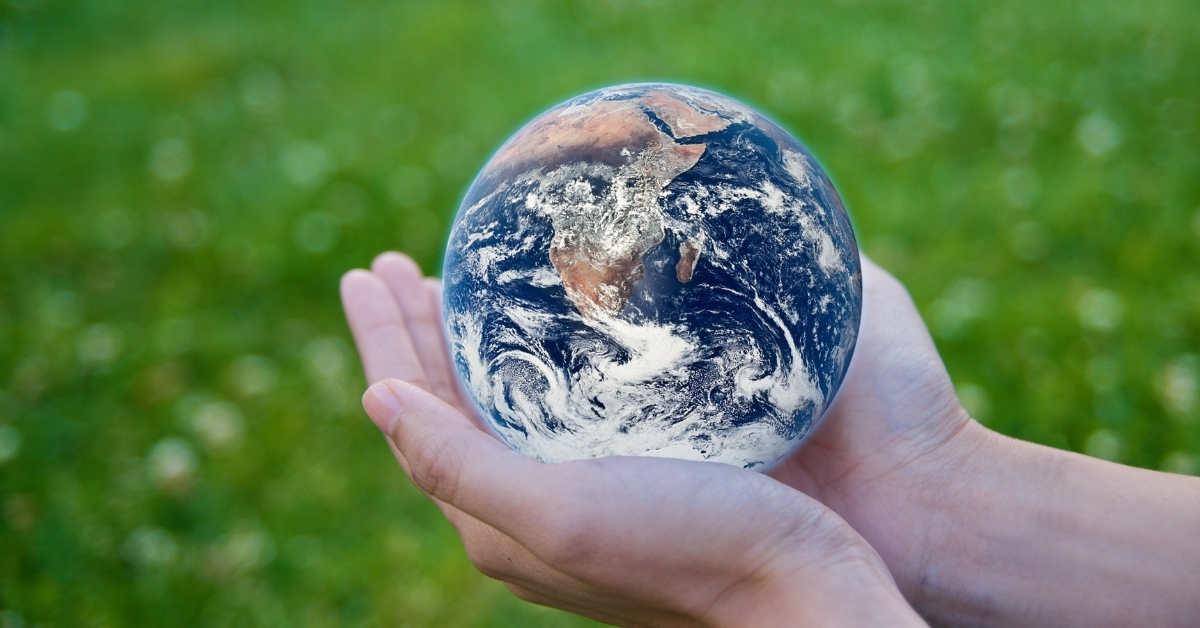a person holding the planet earth with both of his hands